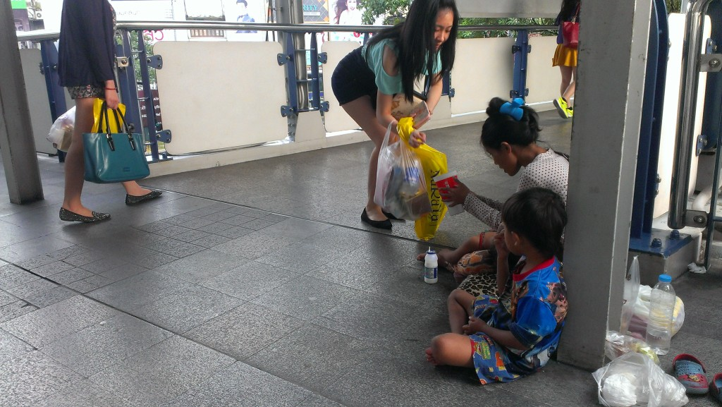 A Cambodian woman with her children was bagging in the front of MBK mall in Bangkok, Thailand on 21 November 2014. Tong Soprach
