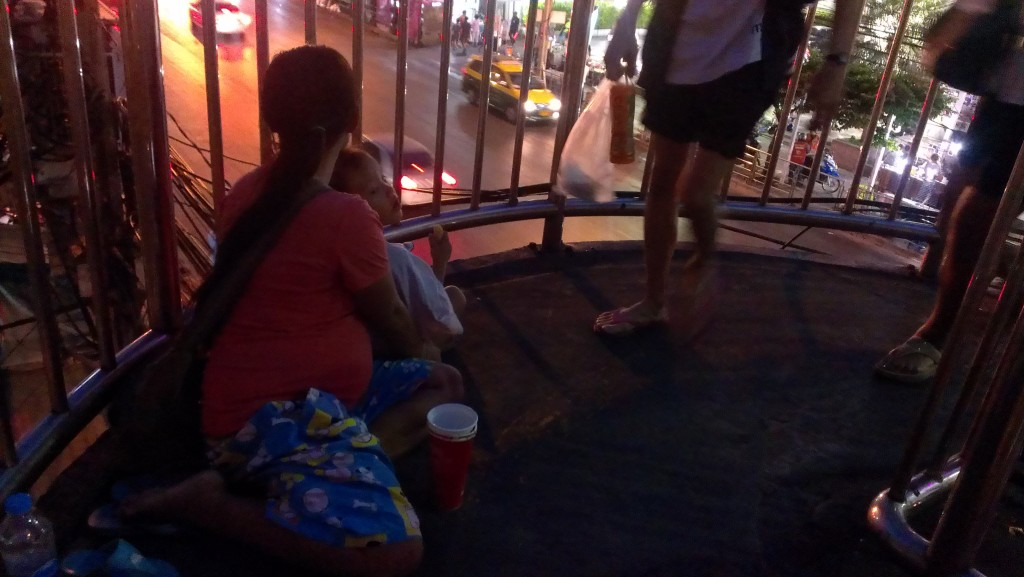A 6-month pregnant Cambodian woman with her son was bagging in the walk stair at the Pratunam area in Bangkok, Thailand on 19 November 2014. Tong Soprach