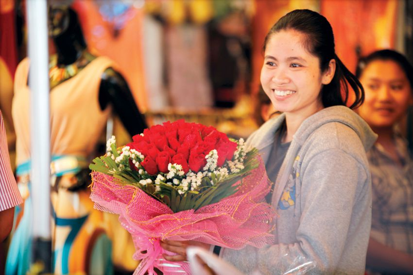 A woman held a branch of flower on the Valentine's Day in 2013. HENG CHIVOAN